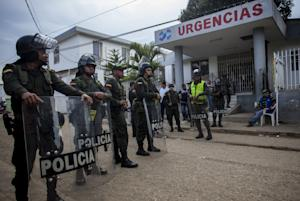 Police stand guard in front of the hospital in Carmen …