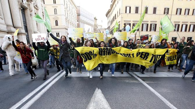 Protesters take part in a rally held the day before the start of the 2015 Paris World Climate Change Conference, known as the COP21 summit, in Rome
