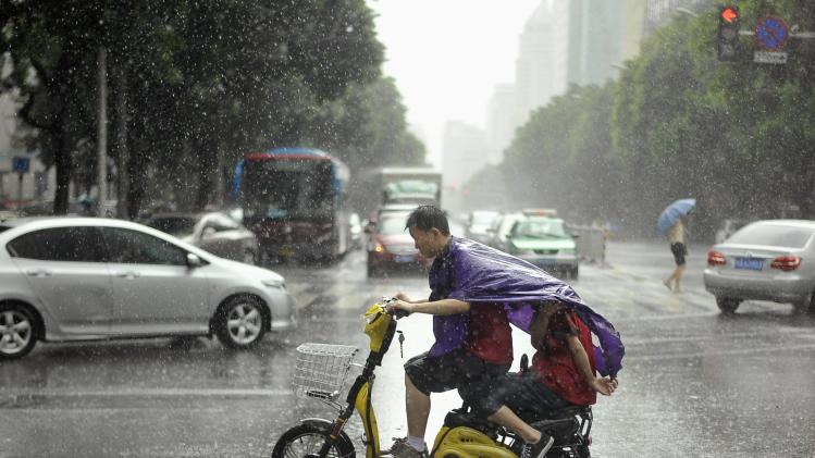 Men ride an electric bicycle during heavy rainfall as Typhoon Matmo lands on Taiwan, in Fuzhou, Fujian province
