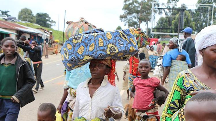 Congolese refugees who fled fighting in Bunagana in DR Congo arrive carrying some of their belongings in the Uganda's side of the border, on October 31, 2013
