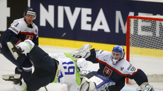 Slovenia's Pance falls in front of Slovakia's Janosik and goaltender Laco during their Ice Hockey World Championship game at the CEZ arena in Ostrava