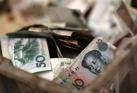 Chinese banknotes are seen at a vendor's cash box at a market in Beijing