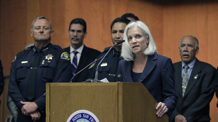 """United States Attorney Melinda Haag, with local law enforcement representatives behind her, announces the arrests of 13 members and associates of the 500 Block/C Street gang during a news conference in South San Francisco, Calif., Thursday, May 3, 2012. Three Immigration and Customs Enforcement agents were shot and injured Thursday while serving """"high-risk"""" warrants in the San Francisco Bay area, authorities said. The agents suffered non-life threatening injuries during an early-morning raid in Petaluma in connection with a 2010 gang-related triple homicide. (AP Photo/Eric Risberg)"""