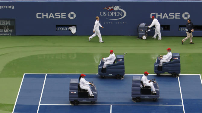 Workers attempt to dry the court at Arthur Ashe Stadium during a rain delay at the U.S. Open tennis tournament in New York, Wednesday, Sept. 7, 2011. (AP Photo/Mike Groll)