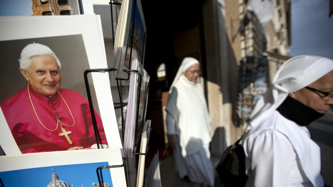 "Two nuns walk past a photo of Pope Benedict XVI as they leave a souvenir shop just outside the Vatican, Tuesday, Feb. 26, 2013. Pope Benedict XVI will be known as ""emeritus pope"" in his retirement and will continue to wear a white cassock, the Vatican announced Tuesday, again fueling concerns about potential conflicts arising from having both a reigning and a retired pope. The pope's title and what he would wear have been a major source of speculation ever since Benedict stunned the world and announced he would resign on Thursday, the first pontiff to do so in 600 years. (AP Photo/Andrew Medichini)"