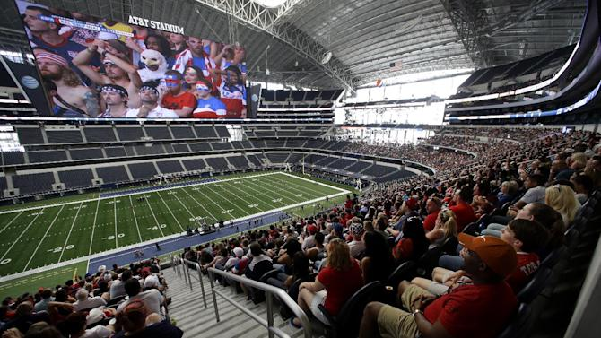 Fans at AT&T stadium watch live coverage on the large video screen of the U.S. Belgium World Cup soccer match, Tuesday, July 1, 2014, in Arlington, Texas
