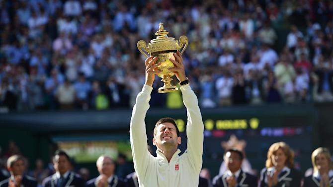 Serbia's Novak Djokovic holds the winner's trophy after beating Switzerland's Roger Federer in the men's singles final match on day thirteen of the 2014 Wimbledon Championships at The All England Tennis Club in Wimbledon, on July 6, 2014