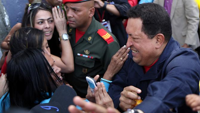 Venezuela's President Hugo Chavez greets people as he arrives to a polling station during the presidential election in Caracas, Venezuela, Sunday, Oct. 7, 2012.  Chavez is running for re-election against opposition candidate Henrique Capriles.  (AP Photo/Rodrigo Abd)