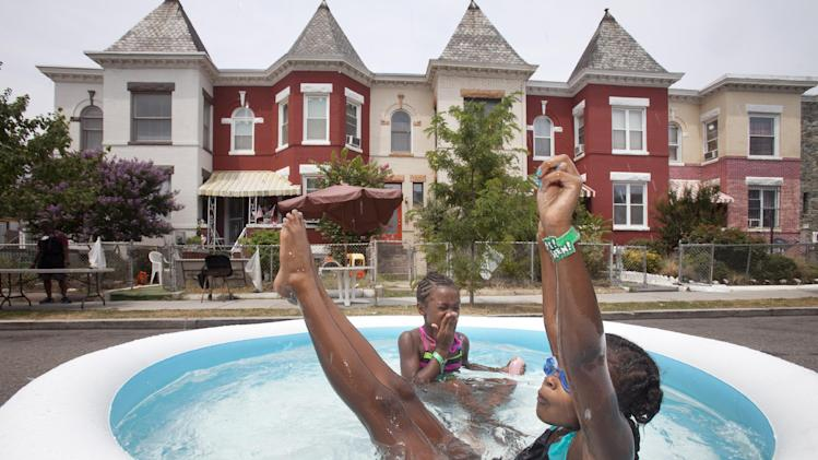 Amari Swint, 8, front, of Philadelphia, and Nia Bailey, 8, of Washington, play in an inflatable pool during the seventh annual block party on Newton Street in northwest Washington, during record heat with temperatures in the triple digits, Saturday, July 7, 2012. (AP Photo/Jacquelyn Martin)