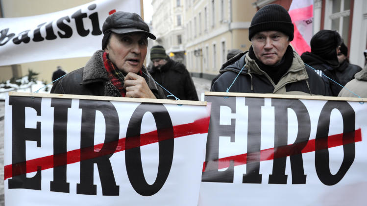 Demonstrators hold posters during a protest at the Latvian parliament in Riga, Latvia, Thursday, Jan. 31, 2013. A small group of protesters gathered outside Latvia's Parliament to heckle lawmakers on their way to vote for changes in a law that will allow the Baltic country to adopt the euro, possibly in January 2014. Recent polls suggest a majority of Latvians are against adopting the euro in light of the debt crisis that has afflicted the eurozone for over three years and fears that the Baltic country will have to help bail out struggling countries. (AP Photo/Roman Koksarov)