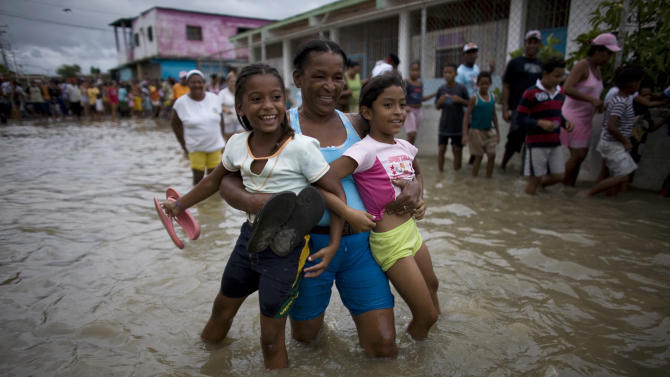 A woman carries two girls through a flooded street in Higuerote, Venezuela, Tuesday Nov. 30, 2010.  Flooding and landslides unleashed by torrential rains have killed at least 30 people in Venezuela and forced thousands from their homes.  (AP Photo/Ariana Cubillos)