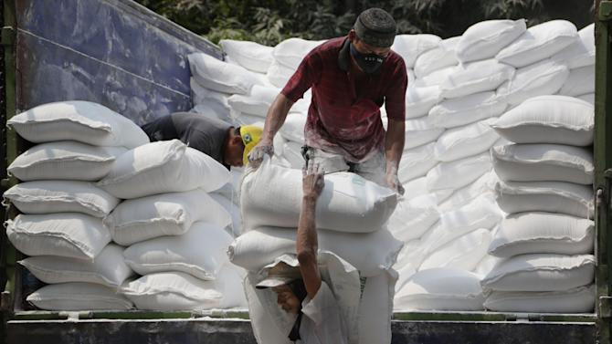 Workers unload sacks of tapioca flour from a truck at a market in Jakarta, Indonesia, Monday, July 6, 2015. (AP Photo/Achmad Ibrahim)