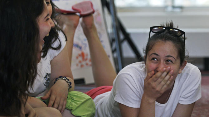 """Amina Sabanova, of Russia, right, laughs with Alla Nogaeva, of Russia, while attending the """"Common Bond"""" summer camp in Newbury, Mass., Wednesday, July 18, 2012.  Teens from across the world who lost loved one due to terrorism gathered for the 10 day camp to share their feelings, insights and a chance to be the world's next generation of international peacemakers. Both girls lost family members in a school hostage crisis in Beslan, Russia during 1994 where more than 350 were killed. (AP Photo/Charles Krupa)"""
