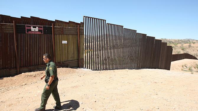 FILE - In this June 19, 2008 file photo, U.S. Border Patrol agent Santos Flores walks in front of a section of old border fence, left, where it meets a five-mile section of new border fence  at the border in Nogales, Ariz. New fencing, more agents and a state crackdown have help drive down the number of illegal immigrants apprehended, but the amount of drugs seized in Arizona has soared at the same time. (AP Photo/Ross D. Franklin, File)
