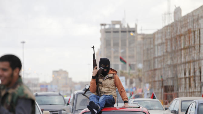 A Libyan masked gunman celebrates on the roof of a vehicle on the early morning of the second anniversary of the revolution that ousted Moammar Gadhafi, in Benghazi, Libya, Sunday, Feb. 17, 2013.  (AP Photo/Mohammad Hannon)