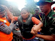 Indonesian military evacuate a woman from a flooded area in Jakarta, on January 18, 2013. The death toll from floods in Indonesia&#39;s capital has risen to 15 after rescuers found another four bodies, a police spokesman said on Saturday as floodwaters receded