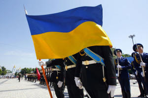 Honor guards hold a Ukrainian national flag during…