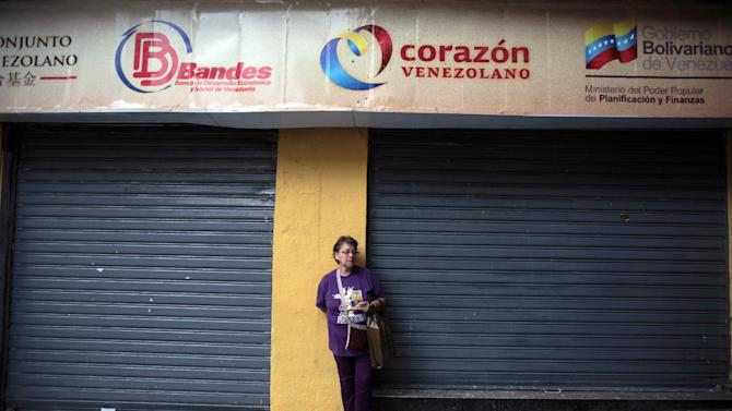 A woman leans against a wall during an outdoor church service in front of the National Assembly, where supporters of Venezuela's ailing President Hugo Chavez gathered to pray for his health in Caracas,Venezuela, Thursday, Dec. 13, 2012.  Venezuelans were warned that Chavez may not be well enough after his fourth cancer-related surgery in Cuba to be inaugurated on Jan. 10.  (AP Photo/Fernando Llano)