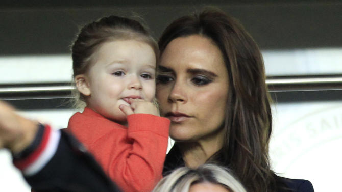 Paris Saint Germain's midfielder David Beckham's wife Victoria Beckham and her daughter Harper, arrive to attend the French League One soccer match between PSG and Brest, at the Parc des Princes stadium, in Paris, Saturday, May 18, 2013. Paris Saint-Germain hopes to strike a deal with David Beckham in the next two weeks in which the former England captain will work with the French club after retirement, possibly in an ambassadorial role. (AP Photo/Thibault Camus)
