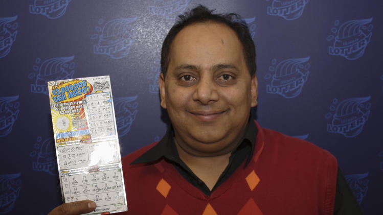 FILE - This undated file photo provided by the Illinois Lottery shows Urooj Khan, of Chicago, posing with a winning lottery ticket. Khan died from cyanide poisoning in July 2012 shortly before collecting $425,000 in winnings. An attorney who represents Khan's widow says most of the businessman's $2 million estate should go to his client, the Chicago Sun-Times reported Thursday, Feb. 7, 2013. (AP Photo/Illinois Lottery, File)