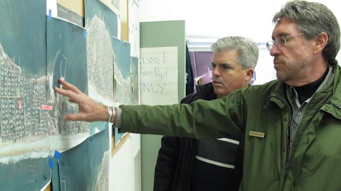 In this Friday, Nov. 16, 2012 photo, Chris Soller, right, superintendent of the Fire Island National Seashore, points to a map of Fire Island with Suffolk County Executive Steve Bellone, in Kismet, N.Y. The two were among a team of officials touring the damaged barrier island south of Long Island. (AP Photo/Frank Eltman)