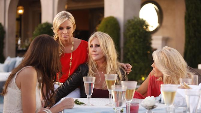 "This undated publicity photo provided by Bravo shows, from left, Heather Dubrow, Tamra Barney, Vicki Gunvalson and Gretchen Rossi, in a scene from ""All Housewives Clam Bake at Rachel's"" in Bravo's Season Eight of ""The Real Housewives of Orange County."" The TV series creator Scott Donlop, who cast Gunvalson, remembers her apprehension about joining the show like it was yesterday. At that point, nobody had any inkling ""The Real Housewives"" would last for eight seasons, let alone ignite a cultural phenomenon. (AP Photo/Bravo, Vivian Zink)"