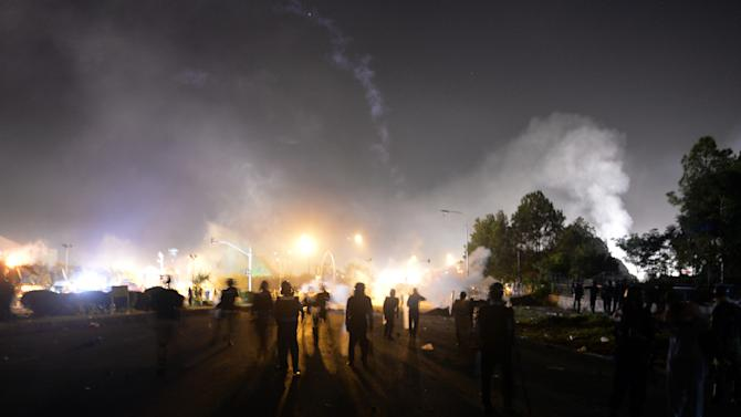 Riot policemen take position during clashes with opposition supporters near the prime minister's residence in Islamabad on August 30, 2014