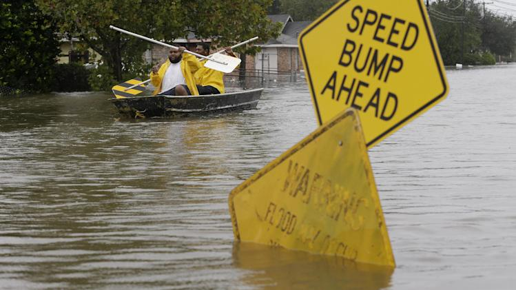 Isaac Fields, left, and Victor Jones use street signs to paddle a boat out of their flooded neighbor, Thursday, Aug. 30, 2012, in LaPlace, La. Isaac has caused major flooding in the region. (AP Photo/Eric Gay)