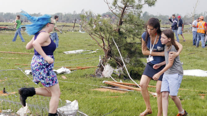 A parent rushes to embrace her child as a teacher escorts her away from Briarwood Elementary school after a tornado destroyed the school in south  Oklahoma City, Okla, Monday, May 20, 2013. Near SW 149th and Hudson.  (AP Photo/ The Oklahoman,  Paul Hellstern)