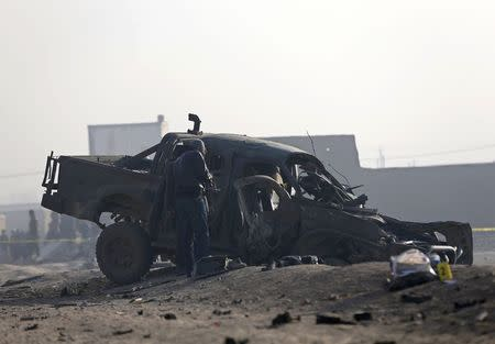 Afghan security forces inspect at the site of a suicide attack in Kabul