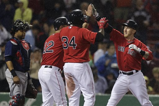 Boston Red Sox' Mike Carp, right, is congratulated by teammates Mike Napoli (12)  and David Ortiz (34) after his three-run home run off Cleveland Indians starting pitcher Justin Masterson during the s