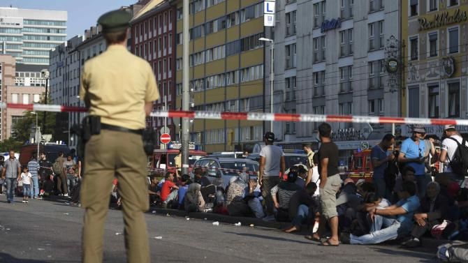 A German policeman watches migrants outside the main railway station in Munich