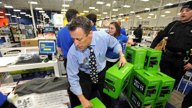 Peter Schultz helps stack a pallet of Xbox One game sets for a doorbuster sale at a Best Buy store just before midnight on Thanksgiving Day, Thursday, Nov. 28, 2013, in Dunwoody, Ga. All of the store's 120 employees were on hand to ring up items after the electronics retailer opened on Thanksgiving this year. (AP Photo/David Tulis)