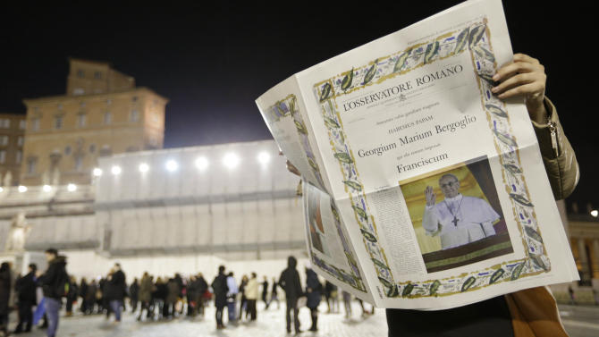 A reader looks at the first edition of the Vatican newspaper L'Osservatore Romano after the election of Pope Francis, the 266th pontiff of the Roman Catholic Church, in St. Peter's Square at the Vatican, Wednesday, March 13, 2013. Cardinal Jorge Bergoglio of Argentina was elected pope. (AP Photo/Alessandra Tarantino)