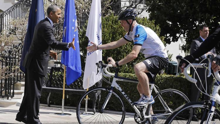 U.S. President Obama prepares to high-five a rider in the Wounded Warrior Project's Soldier Ride at the White House in Washington