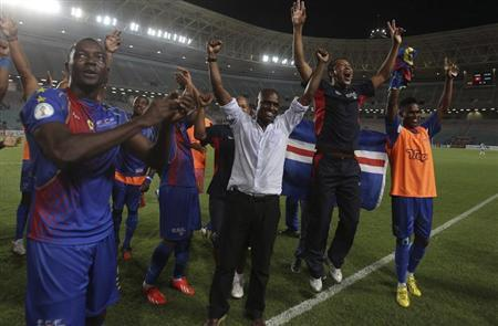 Cape Verde players celebrate with their coach Antunes, after winning their 2014 World Cup qualifying soccer match against Tunisia at the Rades Stadium in Tunis