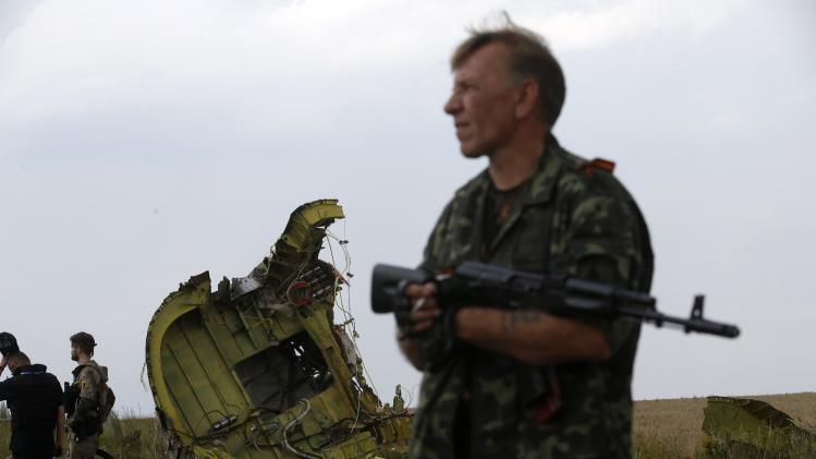 An armed pro-Russian separatist stands guard as monitors from Organization for Security and Cooperation in Europe and members of a Malaysian air crash investigation team inspect the crash site of Malaysia Airlines Flight MH17 near the village of Hrabove