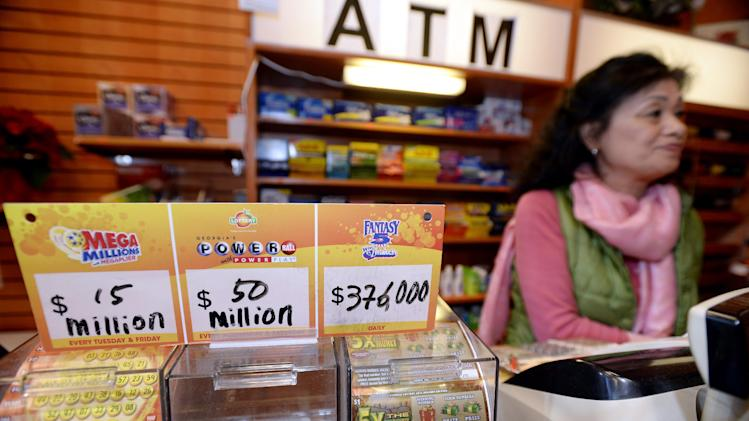 CORRECTS SPELLING OF NAME TO YOUNG SOO LEE, NOT YOUNG SOOLEE - Owner Young Soo Lee tends the counter at her small Alliance Center office building newsstand on Wednesday, Dec. 18, 2013, in Atlanta, after lottery officials said one of two winning Mega Millions lottery tickets were purchased from her store in Tuesday's $636 million drawing,  The store owner said she sold 1300 lottery tickets on Tuesday rather than the normal sales of about 100 tickets. (AP Photo/David Tulis)