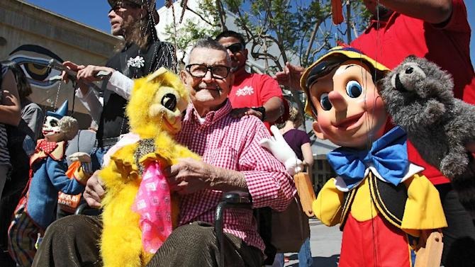 "FILE-This April 6, 2014 file photo shows Bob Baker, who founded The Bob Baker Marionette Theater, leading a parade as the Grand Marshall during the ""Million Puppet March'' in Santa Monica, Calif. Baker, the founder of one of America's oldest puppet theaters, has died. He was 90. (AP Photo/Richard Vogel, File)"