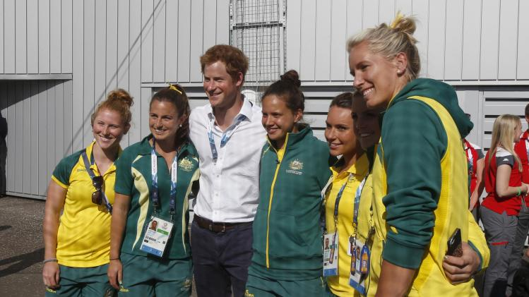 Britain's Prince Harry poses for a photograph with players from the Australian hockey team before the Wales versus Scotland group B preliminary round of the womens hockey during the 2014 Commonwealth Games in Glasgow