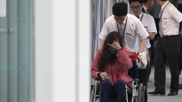 "A passenger of Asiana flight 214 arrives at the Incheon Airport in Incheon, west of Seoul Monday, July 8, 2013. Officials investigating a jetliner crash in San Francisco have determined that Asiana Airlines Flight 214 was traveling ""significantly below"" its target speed as it approached the airport and that the crew tried to abort the landing just before it smashed onto the runway. (AP Photo/Kim Hong-Ji, Pool)"