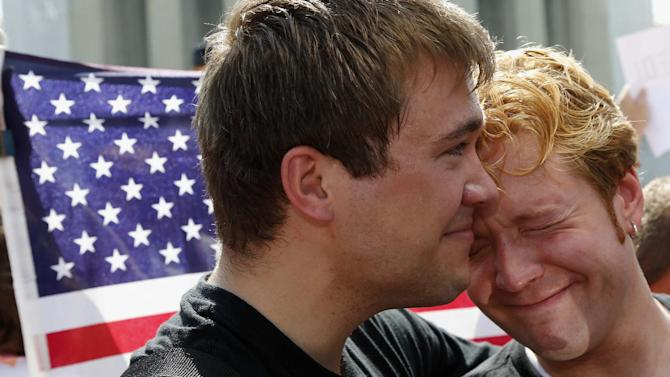 Michael Knaapen, left, and his husband John Becker, right, embrace outside the Supreme Court in Washington, Wednesday, June 26, 2013, after the court cleared the way for same-sex marriage in California by holding that defenders of California's gay marriage ban did not have the right to appeal lower court rulings striking down the ban. (AP Photo/Charles Dharapak)
