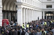 People wait to buy the new iPhone 5 outside the Apple store at Covent Garden in London on September 21. The new phone records in its launch weekend with sales above five million, Apple said Monday, but the figures were below some forecasts and pressured the company's share price