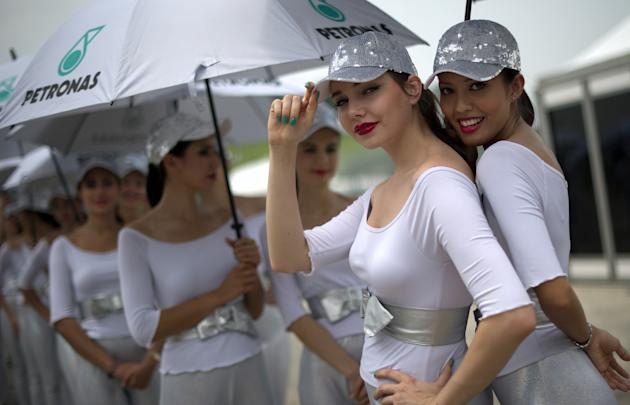 Grid girls pose for the pictures in the paddock area during the qualifying session of Formula One's Malaysian Grand Prix at the Sepang International Circuit in Sepang on March 24, 2012. AFP PHOTO / Sa