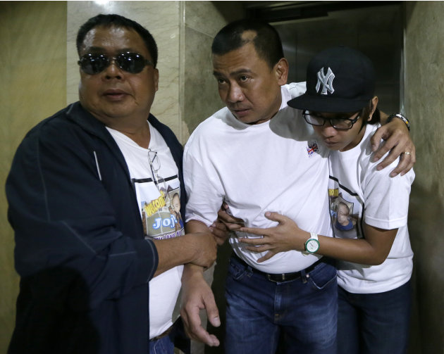 Joseph Balmaceda, center, one of the four Filipino oil field workers who was wounded but survived the terrorist attacks of an oil field in Algeria, limps to his waiting vehicle after talking to the me
