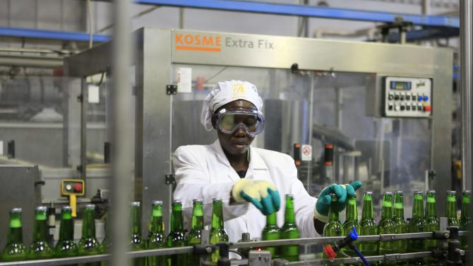 A worker at Keroche Breweries places beer bottles in position at the Naivasha-based plant