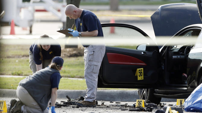 FBI crime scene investigators document the area around two deceased gunmen and their vehicle outside the Curtis Culwell Center in Garland, Texas, Monday, May 4, 2015. Police shot and killed the men after they opened fire on a security officer outside the suburban Dallas venue, which was hosting provocative contest for Prophet Muhammad cartoons Sunday night, authorities said. (AP Photo/Brandon Wade)