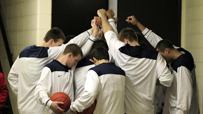 Members of the Penn State basketball team pause before going out onto the court for an NCAA college basketball game against Indiana, Sunday, Jan. 22, 2012, in Bloomington, Ind. Former Penn State football coach Joe Paterno died Sunday morning the family said in a statement. (AP Photo/Darron Cummings)