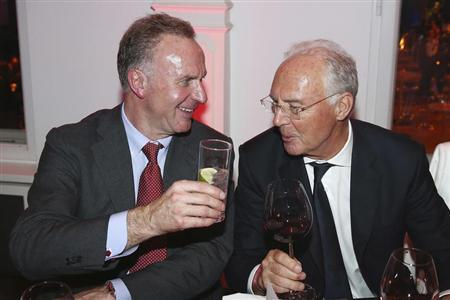 Bayern Munich's CEO Rummenigge and former President Beckenbauer toast each other during the team's victory dinner in Berlin