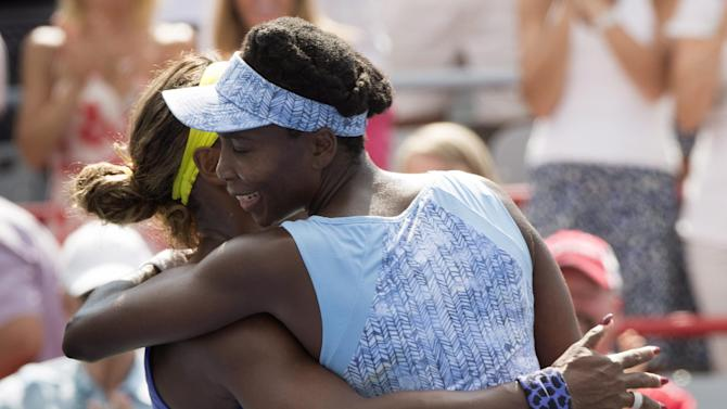 Venus Williams of the United States hugs her sister Serena after beating her 6-7, 6-2, 6-3 during semifinal play at the Rogers Cup tennis tournament Saturday, Aug. 9, 2014, in Montreal